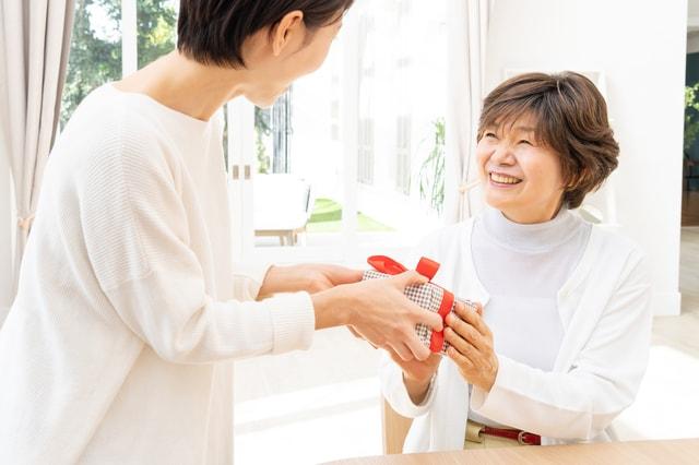 母にプレゼントを渡す娘